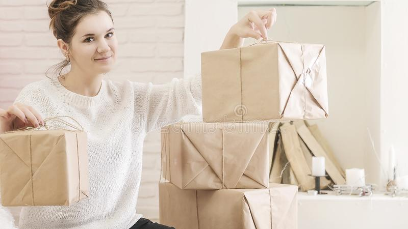A young brunette woman in a white sweater is sitting on the floor in a bright room and examining boxes of gifts. In craft paper.girl opens a box with gifts stock photo