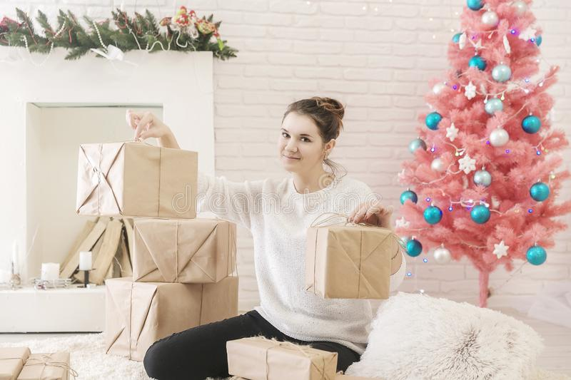 A young brunette woman in a white sweater is sitting on the floor in a bright room and examining boxes of gifts. In craft paper.girl opens a box with gifts royalty free stock photo