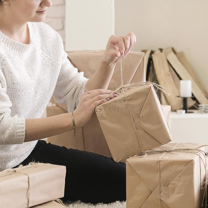 A young brunette woman in a white sweater is sitting on the floor in a bright room and examining boxes of gifts. In craft paper.girl opens a box with gifts royalty free stock image
