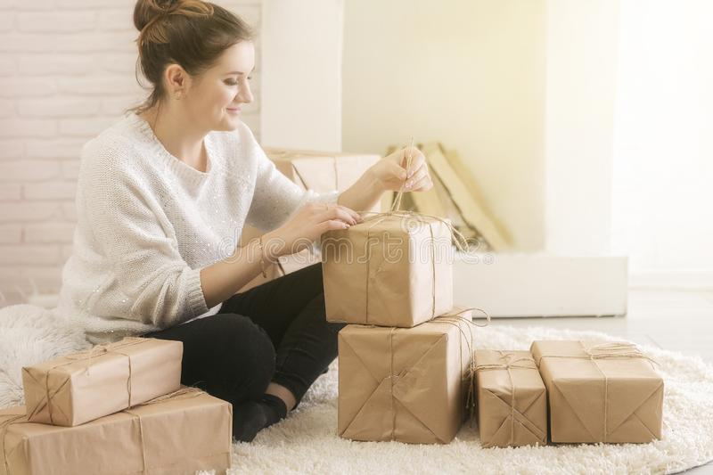 A young brunette woman in a white sweater is sitting on the floor in a bright room and examining boxes of gifts. In craft paper.girl opens a box with gifts stock image