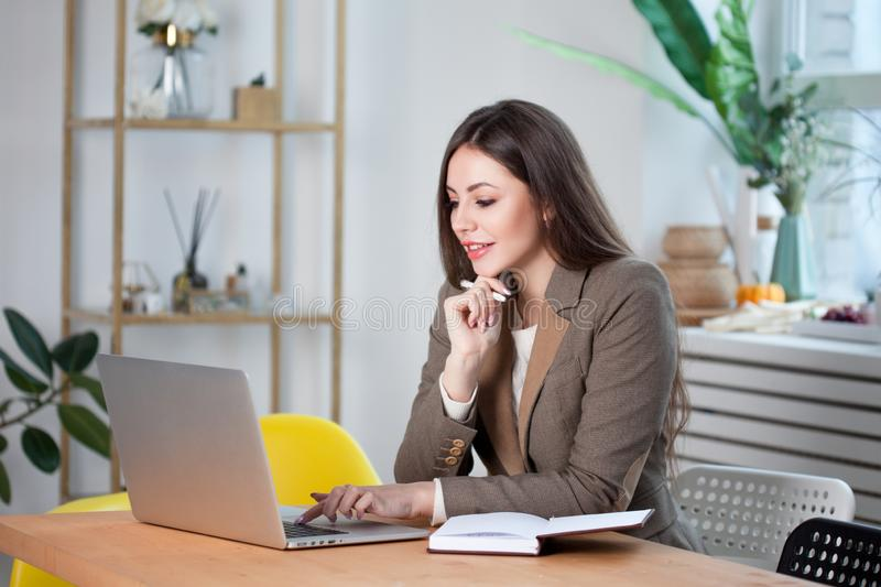 Young brunette woman working on a laptop in a bright comfortable office. stock photos