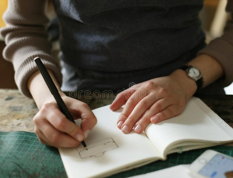 Young brunette woman writes to notebook in sewing workshop, handmade concept. Young woman writes to notebook in sewing workshop, handmade concept royalty free stock photos