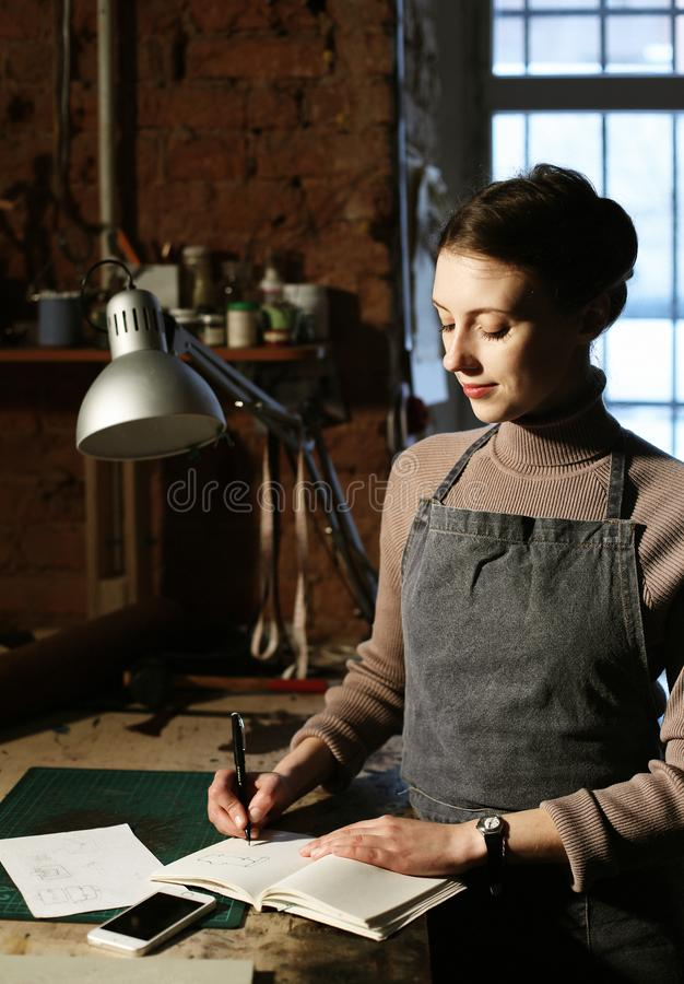 Young brunette woman writes to notebook in sewing workshop, handmade concept. Young woman writes to notebook in sewing workshop, handmade concept stock image
