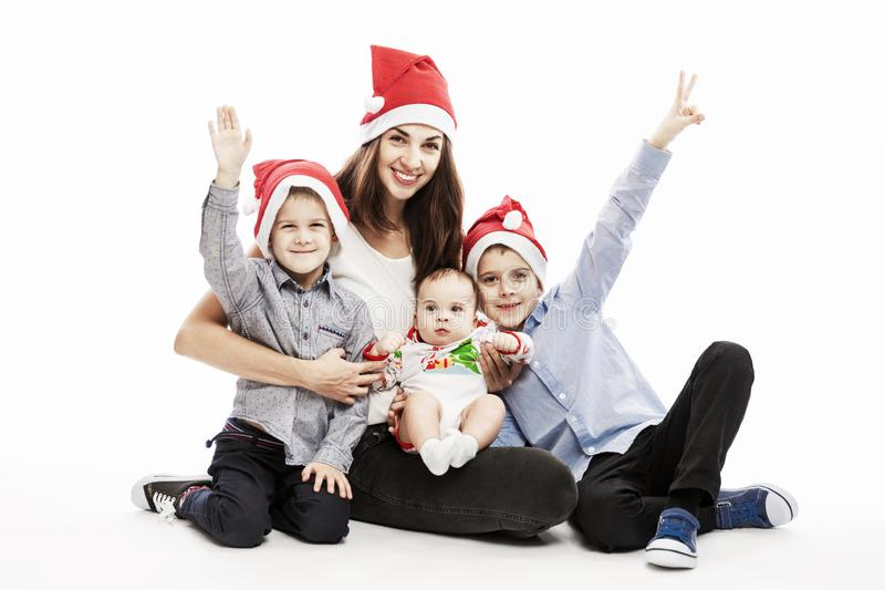 Young brunette woman with three children in Santa hats smiling and hugging. Love and tenderness. Festive mood. White background stock images