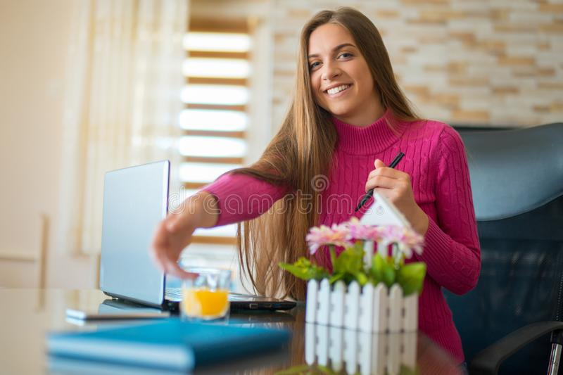 Young brunette working at her office desk with documents and laptop. Businesswoman working on paperwork stock photos