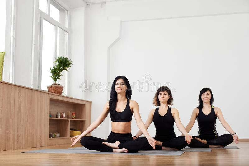 Young women sitting on floor in yoga class, relaxing meditation lotus pose. Copy space. Healthy lifestyle and fitness royalty free stock image