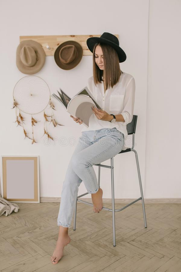Young brunnete girl in black hat, white shirt and blue jeans is reading a magazine in the light boho room royalty free stock image