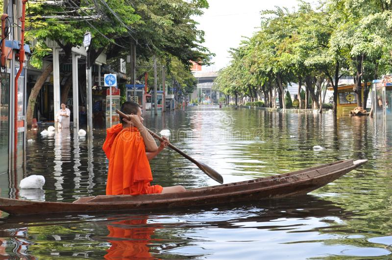 A young buddhist monk keeps smiling as he is rowing his boat in a flooded street of Bangkok, Thailand on the 11th of November 2011 royalty free stock image