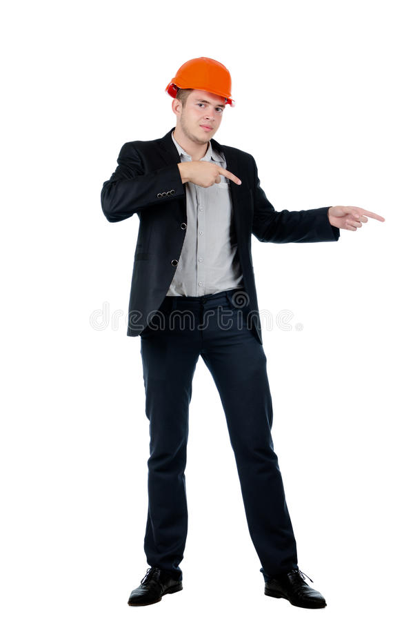 Young builder, architect or engineer pointing. Young builder, architect or engineer in a suit and hardhat standing pointing with both hands to the right of the stock photography