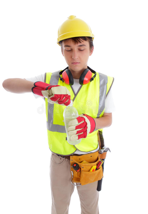 Young builder drinking a bottle of water. Young thirsty builderdrinking a bottle of water. White background stock photos