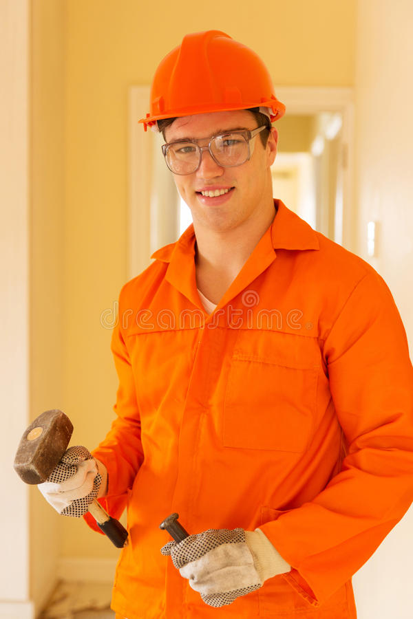 Young builder holding chisel stock photo