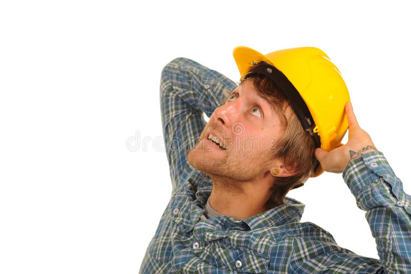 Young builder looking up. A young builder holds his yellow hard hat on his head as he looks upward royalty free stock images