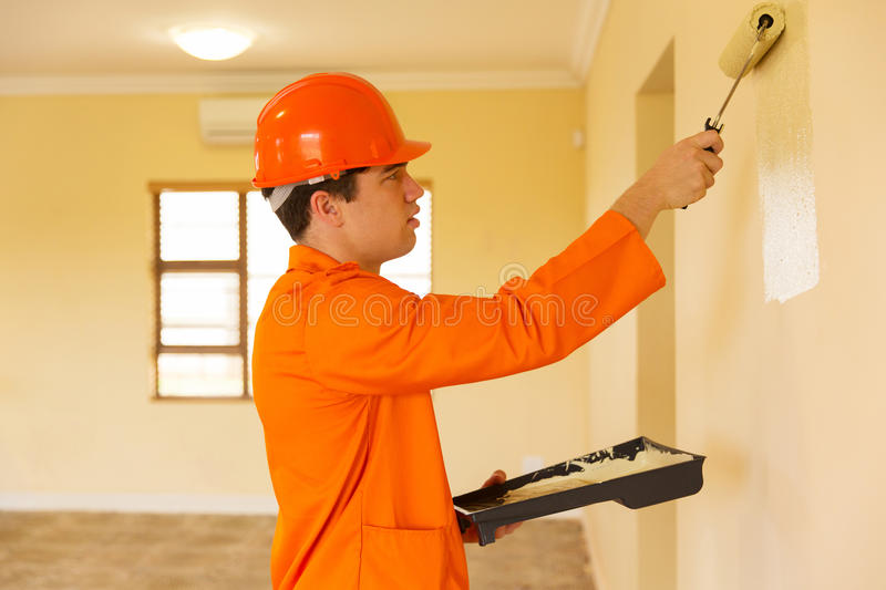 Young builder painting royalty free stock photos