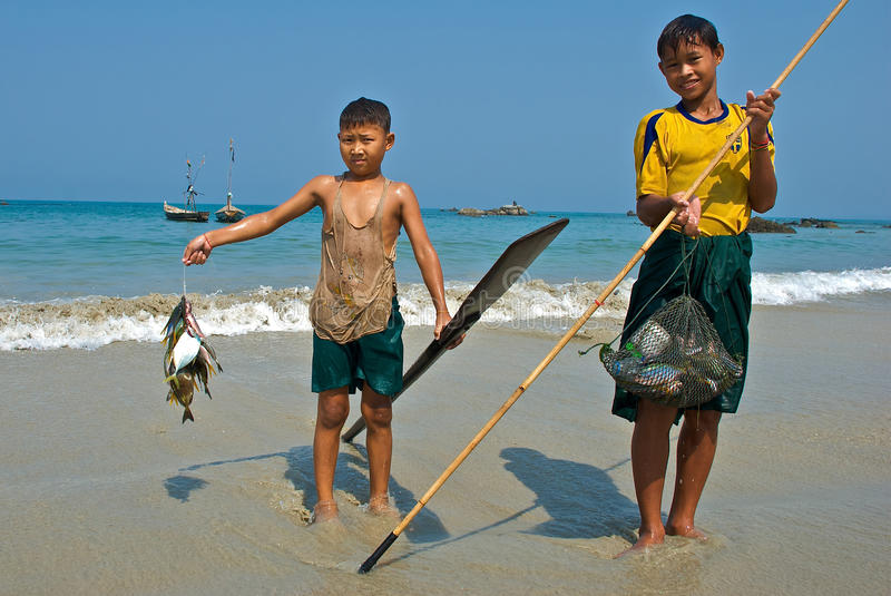 A young Burmese fisherman. Shows his catch of fish. Fishing village royalty free stock images