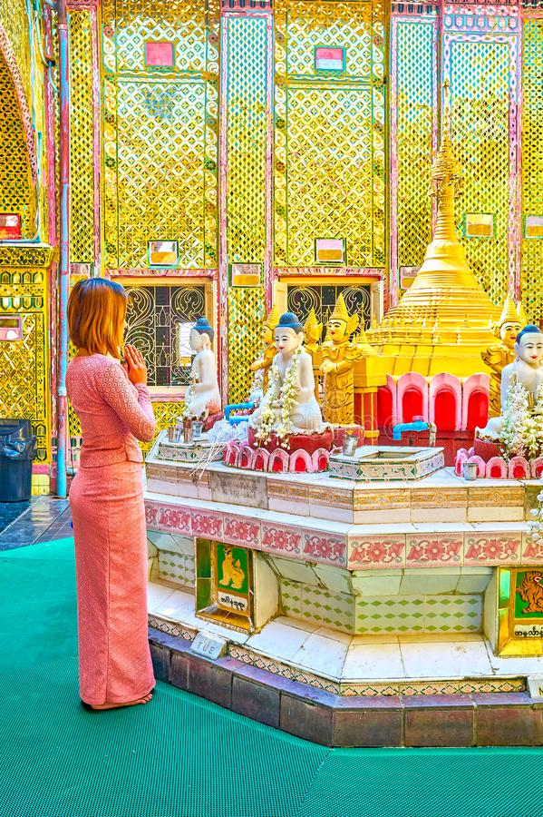 The young Burmese parishioner pray in Su Taung Pyae Pagoda, Mandalay, Myanmar. MANDALAY, MYANMAR - FEBRUARY 23, 2018: The young Burmese prayer pray at the altar stock images