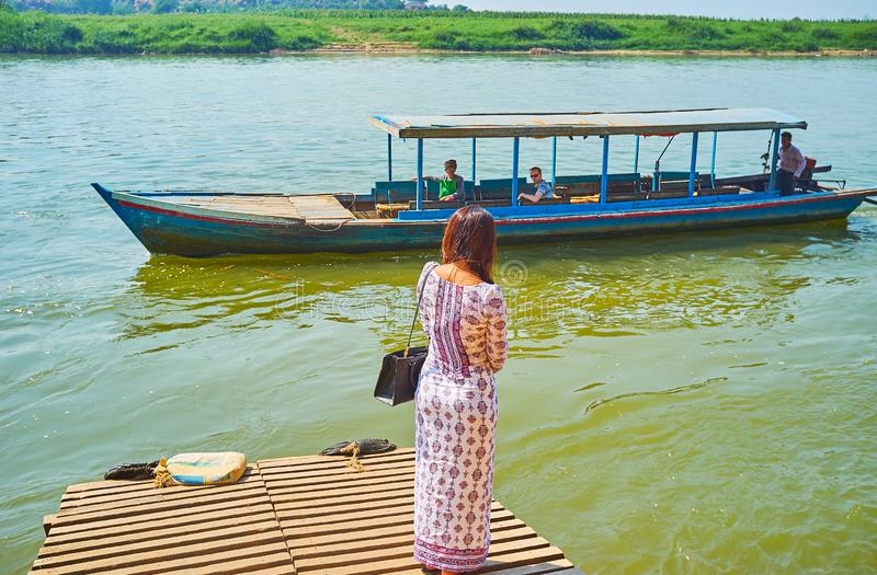 The young Burmese woman weits the ferry to Ava royalty free stock image