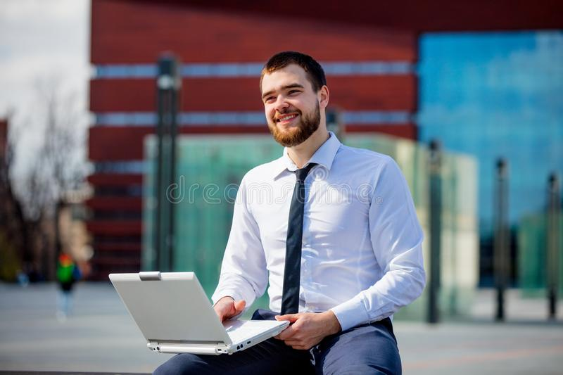 Young businesman with laptop computer stock image