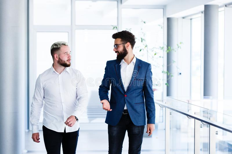Young Business Colleagues Discussing While Walking royalty free stock photos