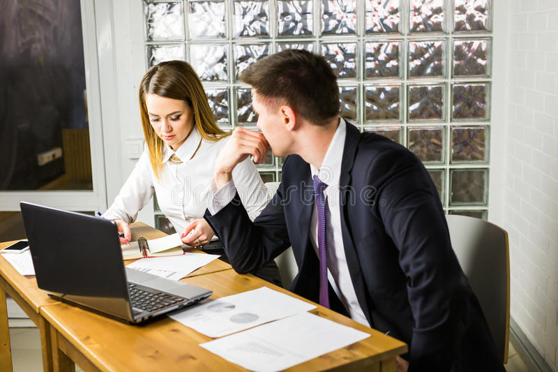 Young business colleagues discussing work on a laptop computer in co-working space, corporate businesspeople royalty free stock image