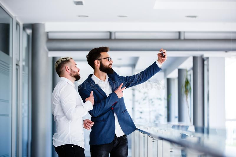 Young Business Colleagues Taking Selfie At Workplace royalty free stock photos