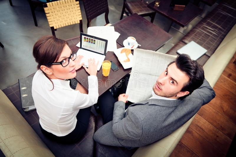 Young Business Couple In A Cafe. A young business couple is discussing important figures over their breakfast royalty free stock photos
