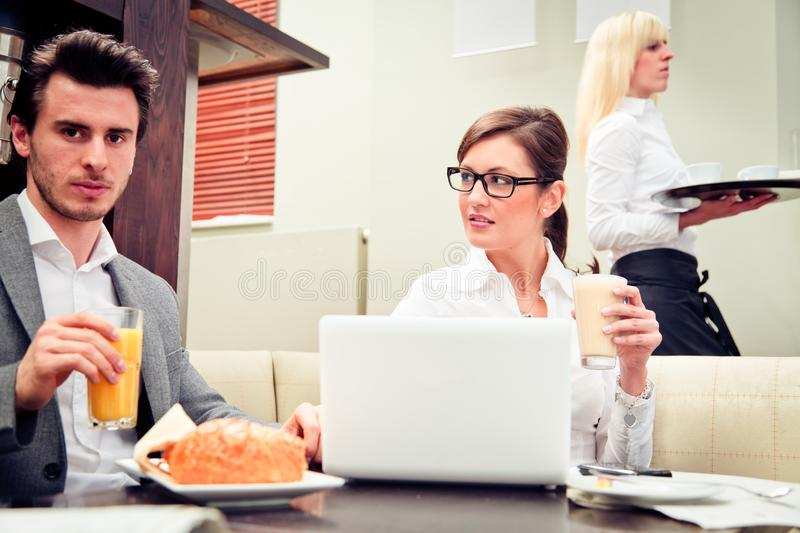 Young Business Couple In A Cafe. A young business couple is discussing important figures over their breakfast stock photography