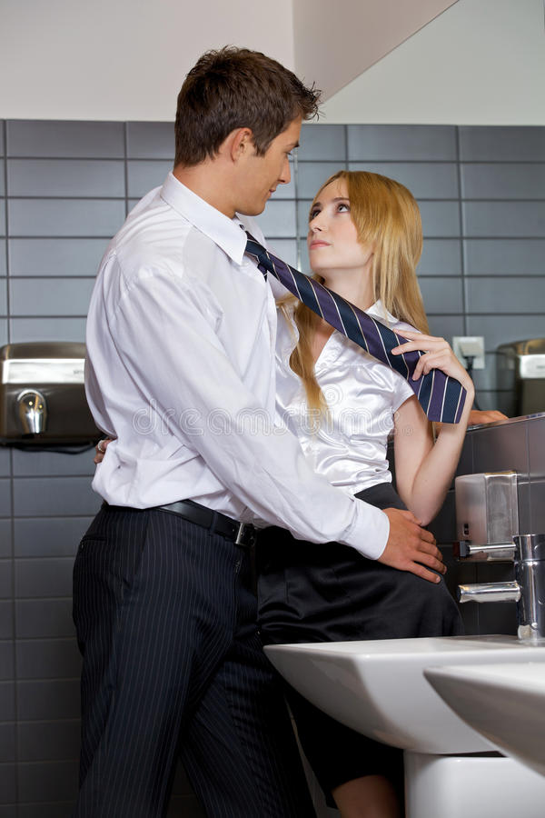 Young business couple flirting with each other at office washroom royalty free stock image