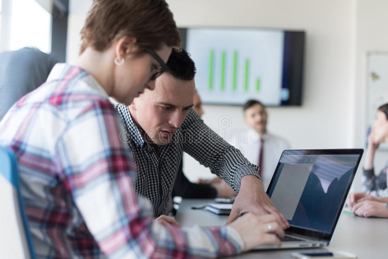 Young business couple working on laptop, businesspeople group on. Young startup business people, couple working on laptop computer, businesspeople group on stock photo