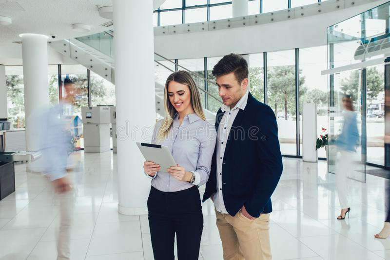 Business couple working on tablet. Motion blur. Young business couple working on tablet. Motion blur royalty free stock images
