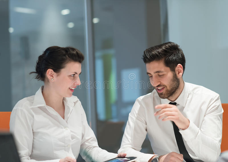 Young business couple working together on project. Young couple working together on tablet computer. Teamwork, help, support concept. Business group at modern royalty free stock photo