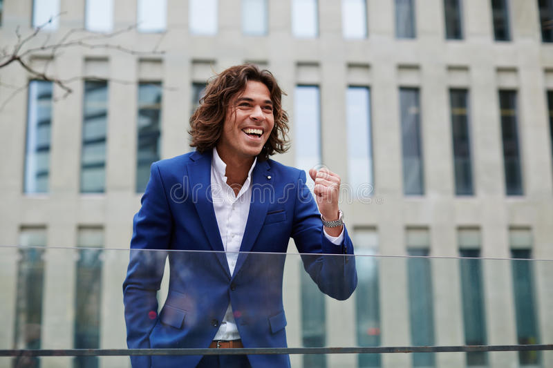 Young business executive celebrating his success standing outdoors stock photo
