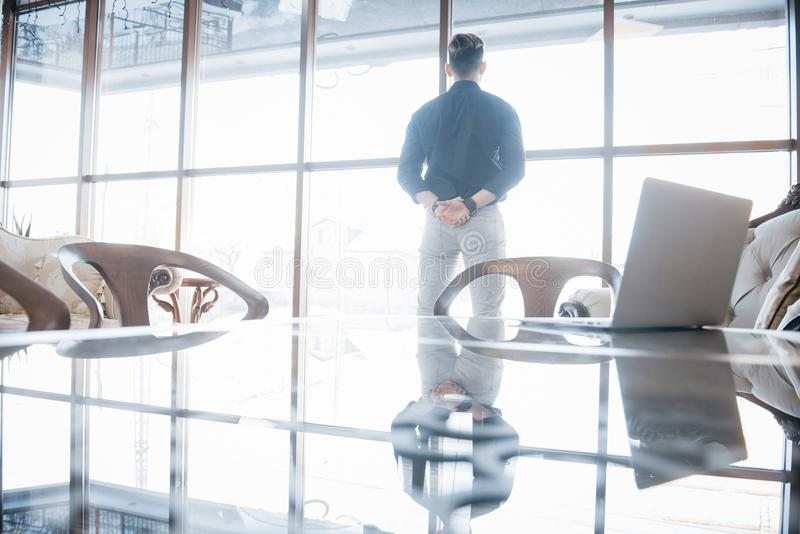 Young business executive and leader standing confidently, in the the top floor office, looking at the city below through stock photos