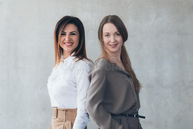 Young business ladies smiling friends colleagues stock photos