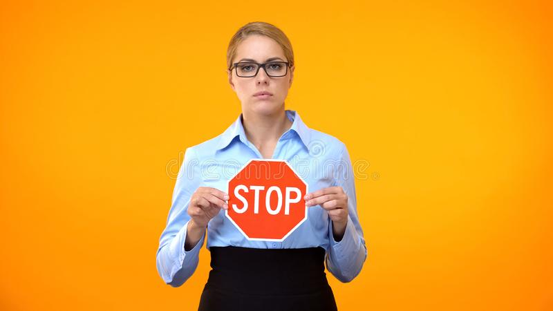 Young business lady holding stop sign hands, sexual harassment at work, protest royalty free stock image
