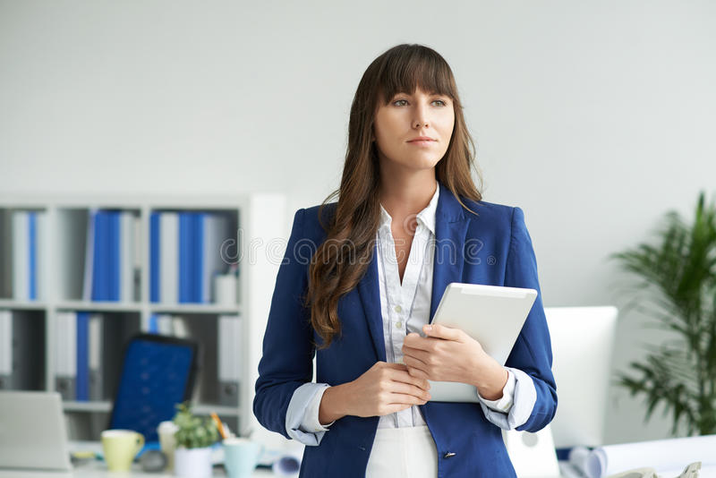 Young business lady. Portrait of young business lady with digital tablet standing in the office royalty free stock photography