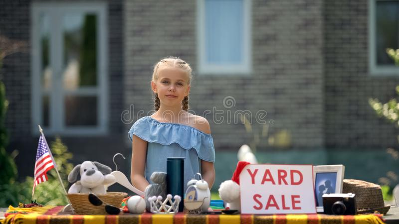 Young business lady selling old toys on yard sale, earning extra pocket money royalty free stock images