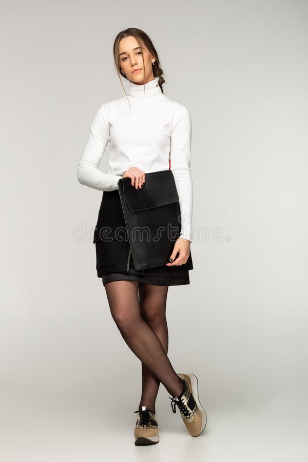 Young business lady in white golf, posing in the studio royalty free stock image