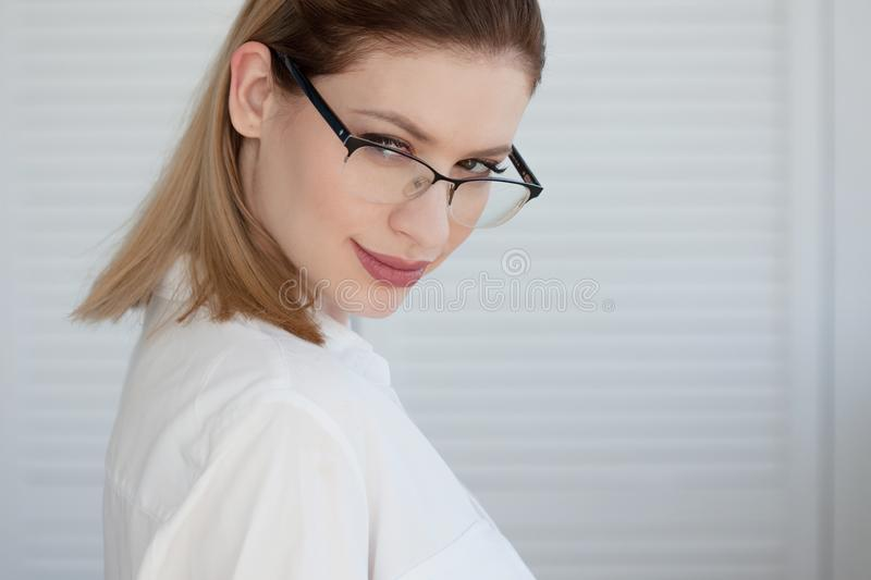 Young business lady in white shirt and glasses. Attractive young woman smiling stock image