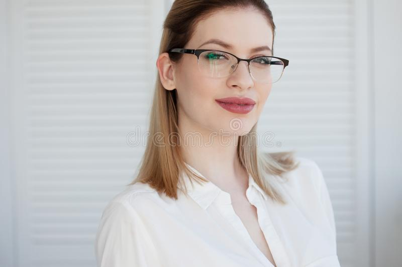 Young business lady in white shirt and glasses. Attractive young woman smiling royalty free stock photos