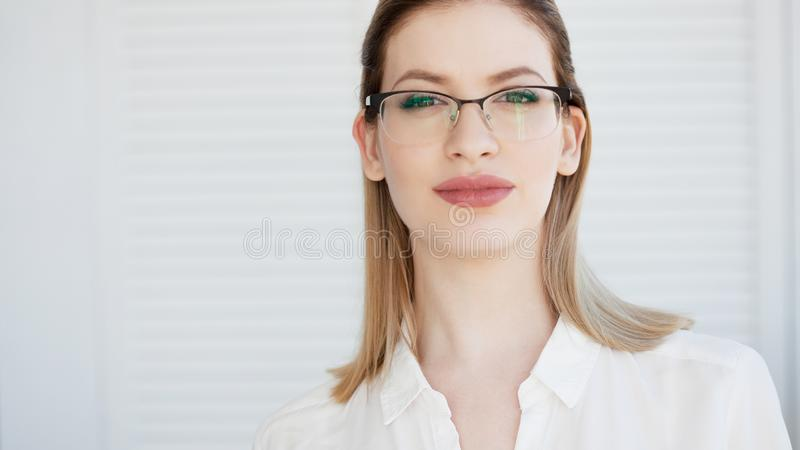 Young business lady in white shirt and glasses. Attractive young woman smiling royalty free stock photography