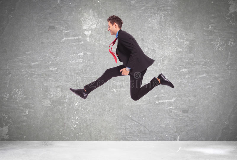 Young business man in a big run. Over a gray background royalty free stock photos