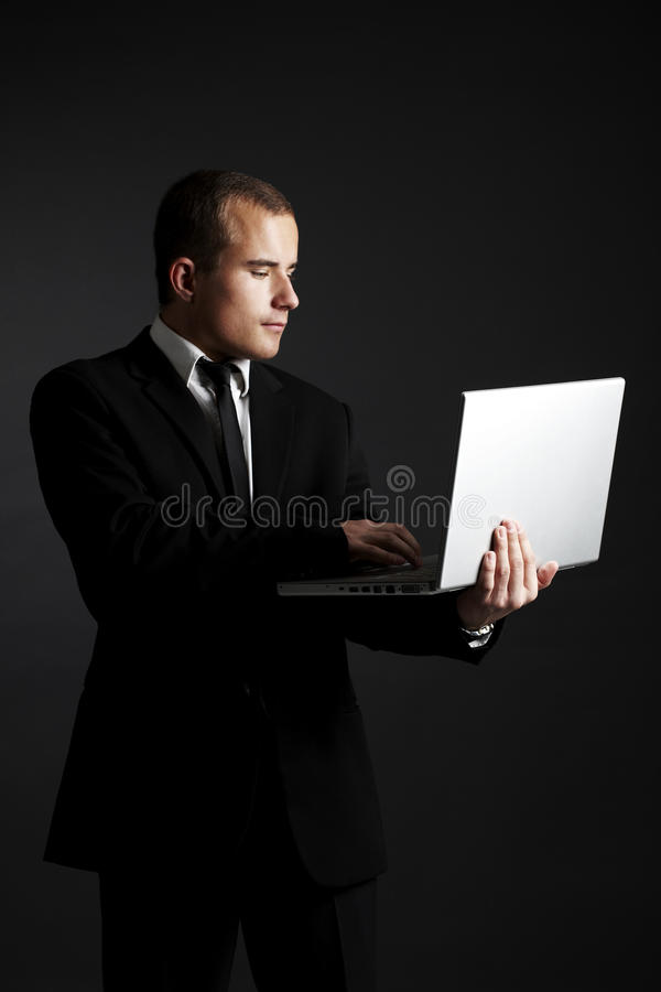 Young business man on black with laptop stock image