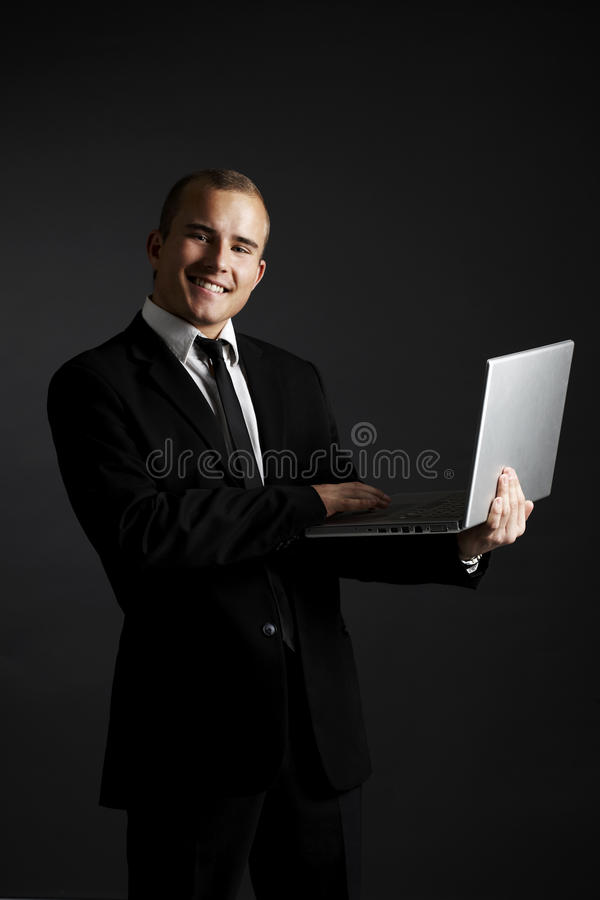 Young business man on black with laptop royalty free stock photography