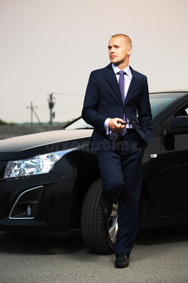 Young businessman with a cell phone leaning on his car stock photography