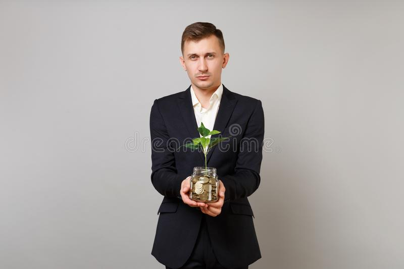 Young business man in classic black suit shirt holding pile gold coins in glass jar with green plant sprout isolated on royalty free stock photos