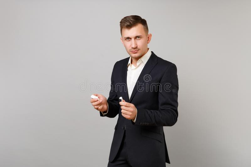 Young business man in classic black suit shirt holding wireless earphones with charging case isolated on grey wall royalty free stock images