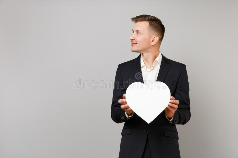 Young business man in classic black suit, shirt looking aside holding white heart with copy space isolated on grey royalty free stock photo