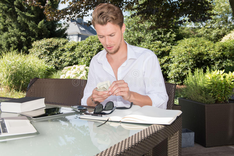Young business man is counting dollars in the garden stock photos