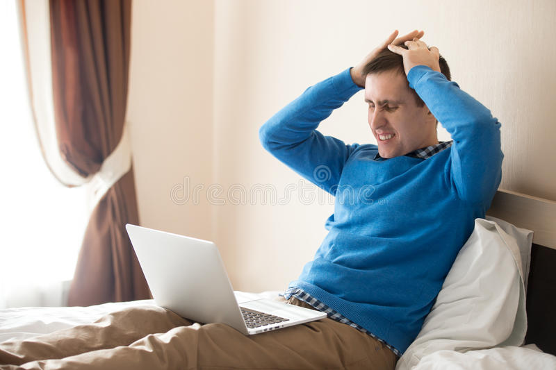 Young business man in dismay. Portrait of young stressed man sitting on bed with laptop wearing smart casual clothing, holding his head in hands with frustrated stock photo