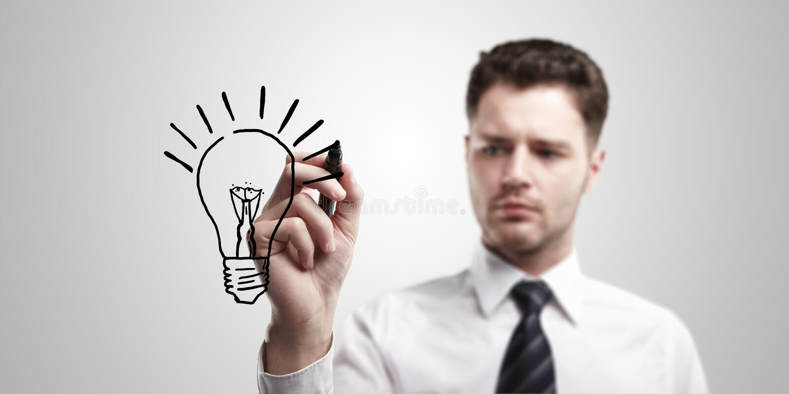 Young business man drawing a light bulb